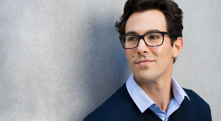 Smiling guy wearing glasses looking away and leaning on grey wal